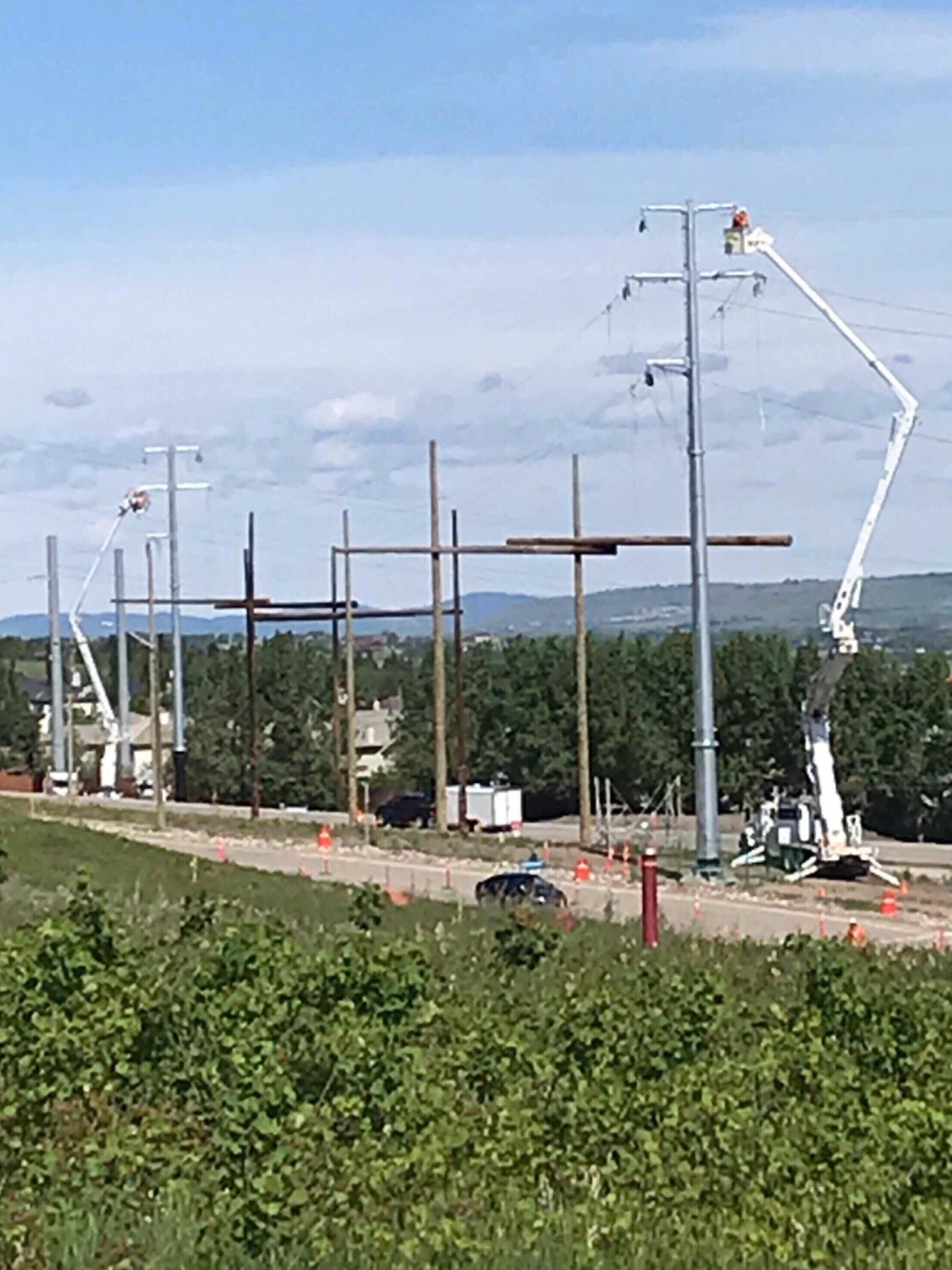 Altalink utility relocates bucket trucks and poles