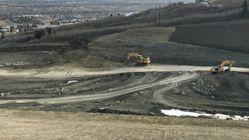 Looking east across the slope where excavators are preparing the area