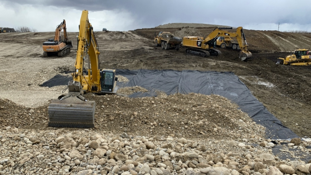 The geotextile fabric is covered with gravel that will provide the foundation for the culvert pipe